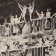 June 20, 1929. Two shots at the Grauman's Theater premiere of 'Hollywood Revue of 1929.' With live girls on the billboard.