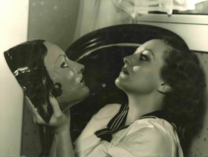 1931. In her dressing room, shot by Hurrell. With mask made by actor Richard Cromwell.