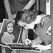 1933. Signing autographs for extras on the set of 'Dancing Lady.'