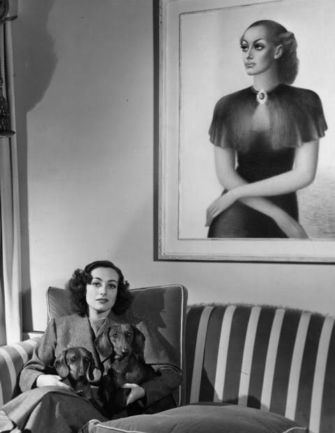 1936. Joan at home, with painting by Edward Biberman.
