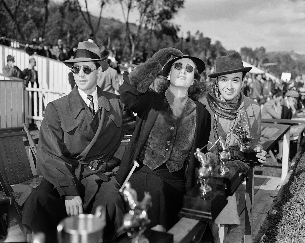 November 1936. At a Los Angeles polo match with husband Franchot Tone, left.