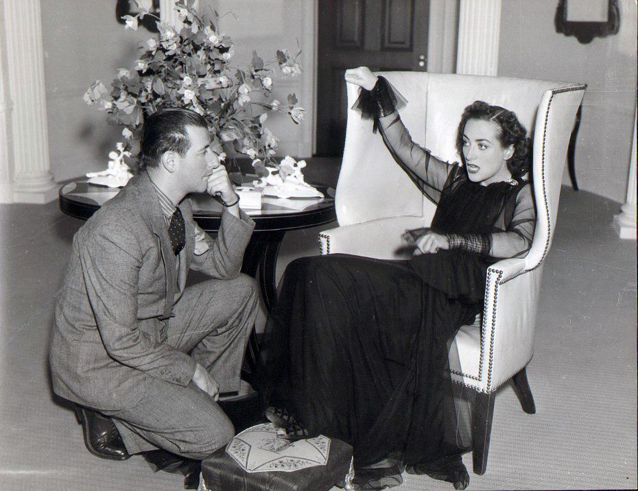 1937. On the set of 'The Last of Mrs. Cheyney' with designer Adrian.