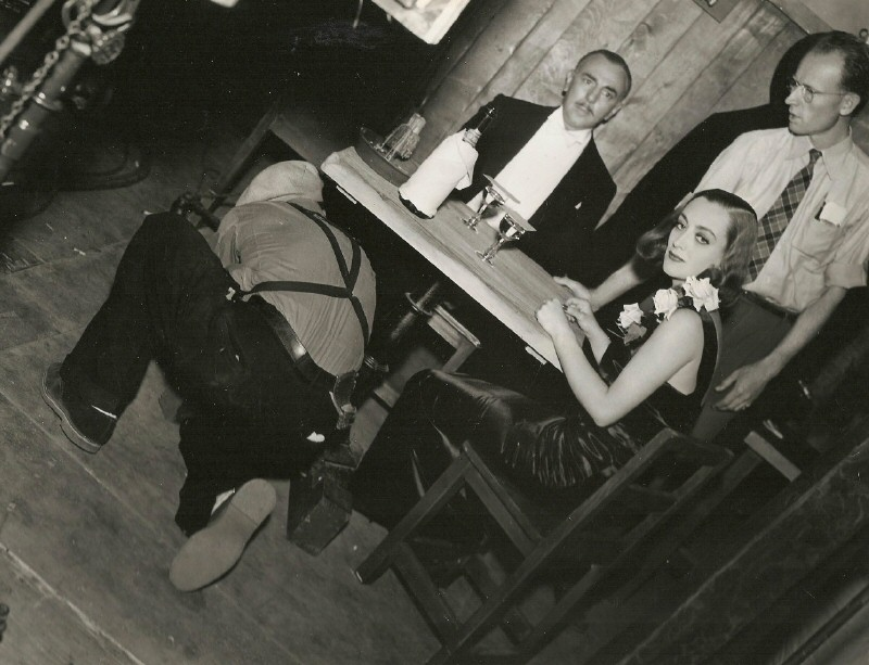1937. On the set of 'The Bride Wore Red.' Prop man Harry Edwards under the table.