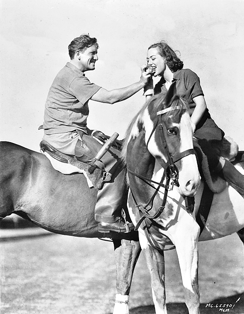 February 1938, with Spencer Tracy. (Her polo pony is a gift from him.)