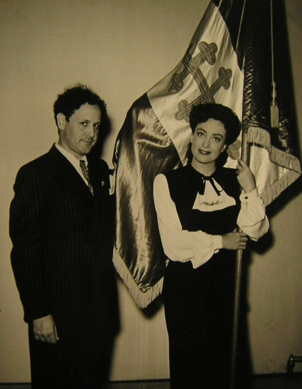 1942. On the set of 'Reunion in France' with Sylvane Robert and the flag of the Free French Republic.