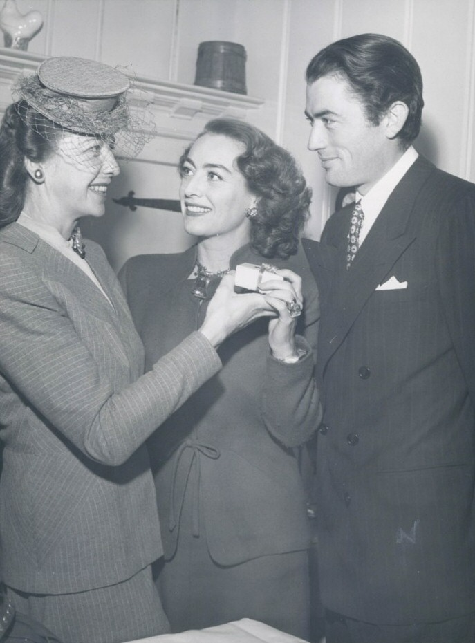 December 1945. With Gregory Peck, receiving the Golden Apple award from the Hollwyood Women's Press Club's Kay Proctor.