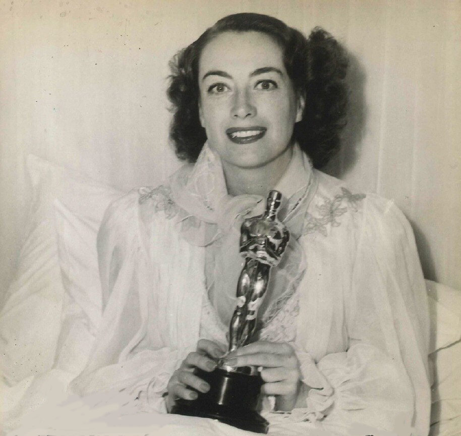 1946. At home, holding her new Oscar for 'Mildred Pierce.'