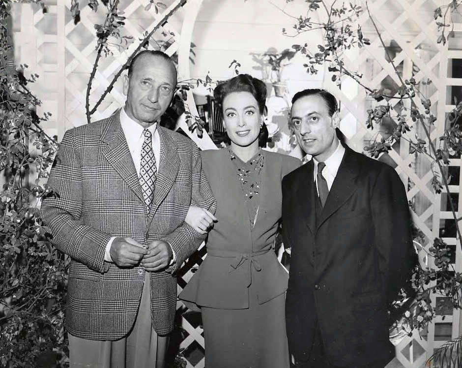 February 1945. On the set of 'Mildred Pierce' with director Curtiz and French Underground publisher Stephen Pizella.