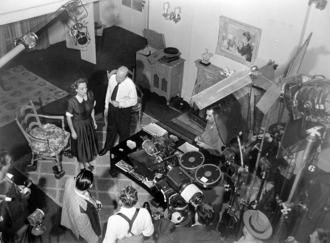 1947. On the set of 'Daisy Kenyon' with director Otto Preminger and crew.