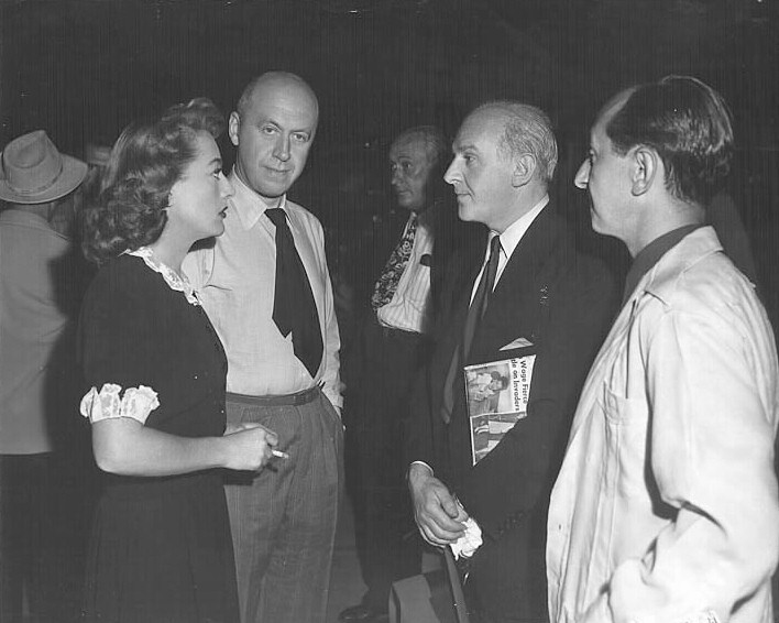 1947. On the set of 'Daisy Kenyon' with director Preminger and Walter Winchell.