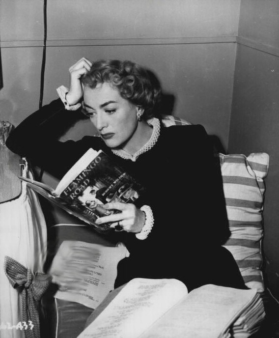 1949. On the set of 'Flamingo Road,' reading the novel by Robert Wilder.