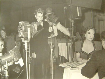 1950. On the set of 'Damned Don't Cry,' with singer Marion Morgan.