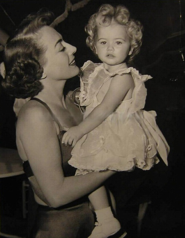1950. On the set of 'The Damned Don't Cry' with unknown tot.