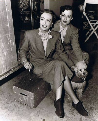1950. 'Harriet Craig.' On the set with her stand-in. And poodle. And booties.
