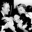 1953. With Michael Wilding and their poodles Cliquot and Titi. Includes press caption.