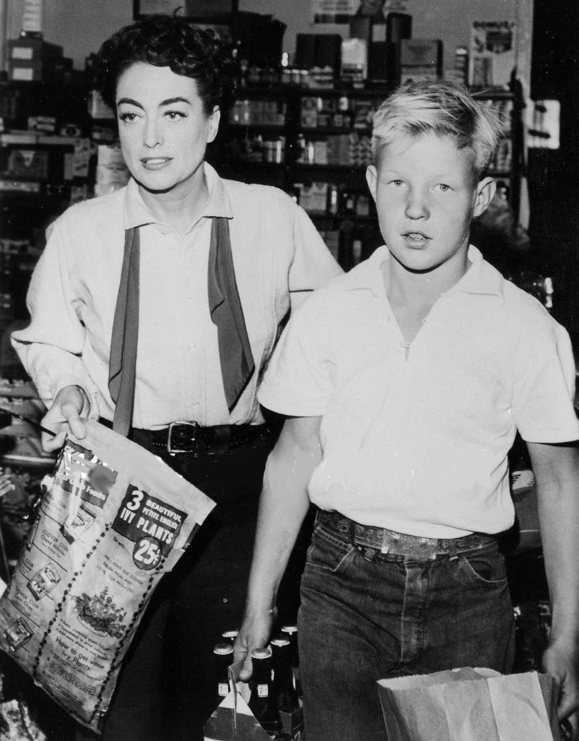 1954. On the set of 'Johnny Guitar' with son Christopher.