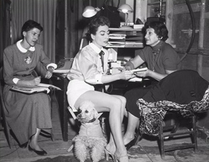 1955. On the set of 'Female on the Beach' with secretaries. (Thanks to Shane.)