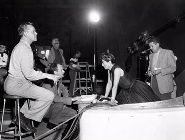 1955. On the set of 'Female on the Beach' with director Joseph Pevney, left. (Thanks to Shane.)
