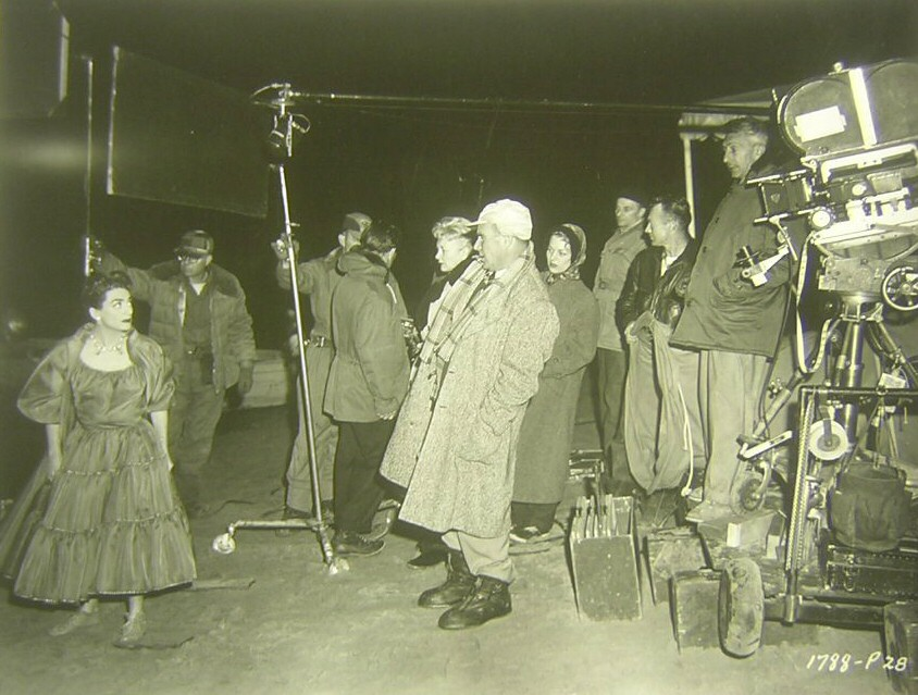 1955. On the set of 'Female on the Beach' with cinematographer Charles Lang (in the white cap).
