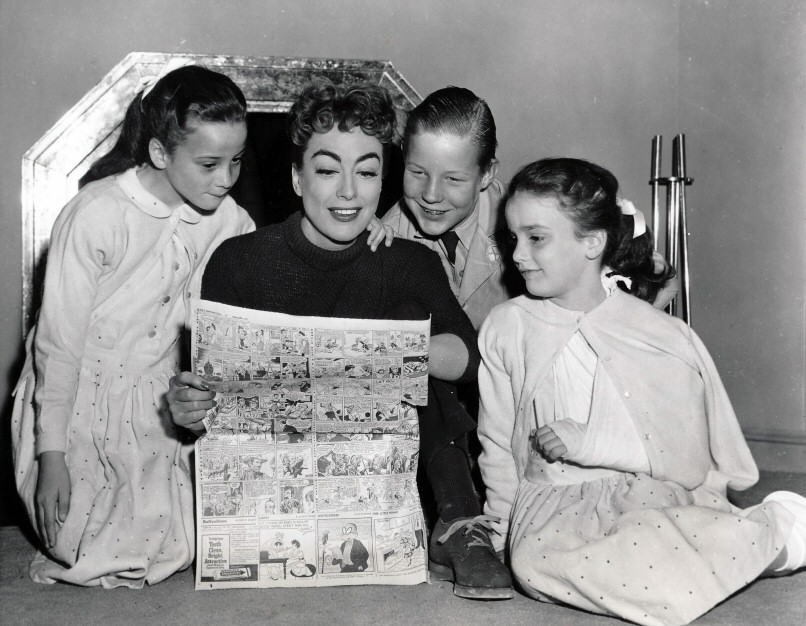 1955. On the set of 'Female on the Beach' with Christopher and the twins.