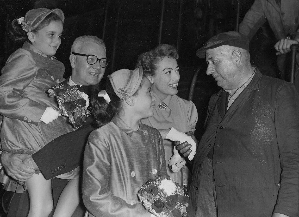 August 1956 at London's Paddington Station with husband Al Steele, twins, and train conductor.