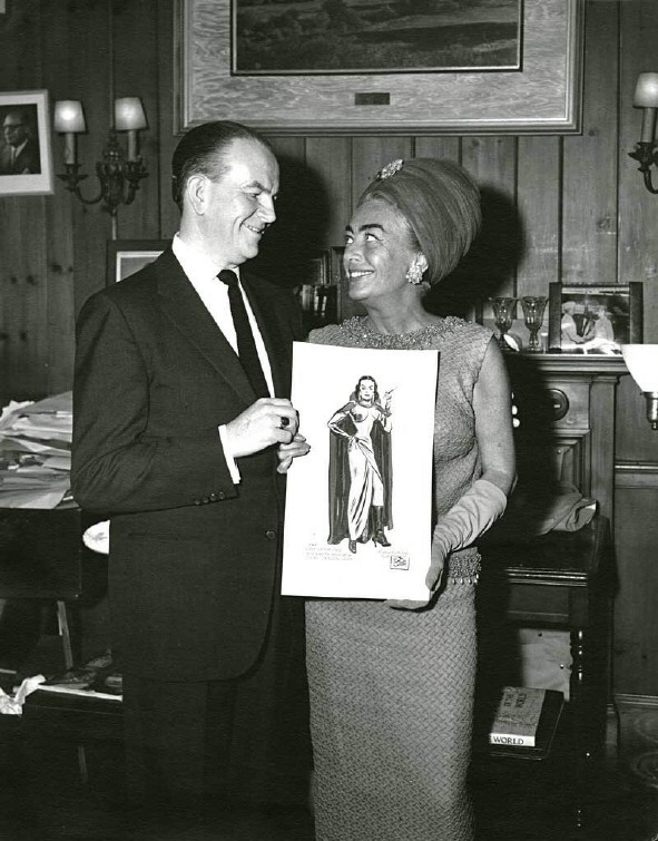 1964. Cartoonist Milton Caniff presents Joan with a 'Dragon Lady' birthday greeting.