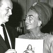 1964. Cartoonist Milton Caniff presents Joan with a 'Dragon Lady' birthday card.