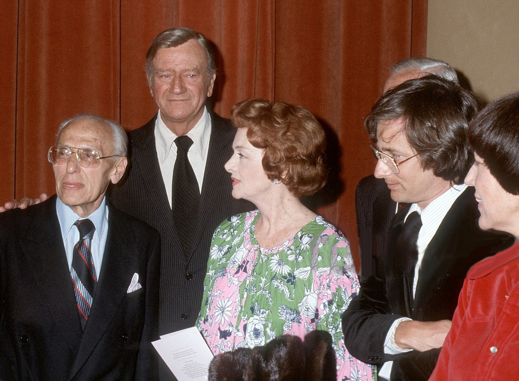 June 24, 1977. At the Samuel Goldwyn Theater tribute to Joan organized by George Cukor. From left: Cukor, John Wayne, Myrna Loy, Steven Spielberg.