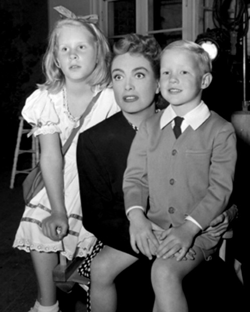 1947. On the set of 'Daisy Kenyon' with kids Christina and Christopher.