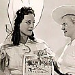 On the set of 'Hussy,' Texan Joan receives a certificate from a Rangerette in honor of Texas's 100th year of independence. Clicking this link will take you to 2 pictures.