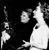 Joan delivers the Oscar to Bancroft on the set of Bancroft's Broadway show 'Mother Courage and Her Children.' May 1963.