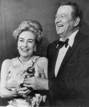 John Wayne presents Joan with the 1969 DeMille award at the '70 Golden Globes