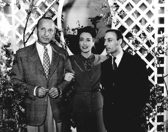 1945. On the set of 'Mildred Pierce,' with director Curtiz, left.